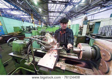 Senior milling machine operator works at machine