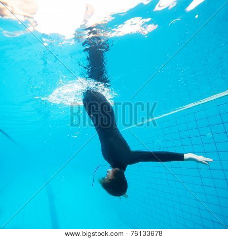 Female Diving Downwards In Swimming Pool