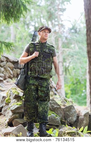 hunting, war, army and people concept - young soldier, ranger or hunter with gun walking in forest poster