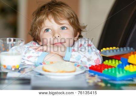 Little Kid Boy Drinking Milk And Playing With Construction Blocks