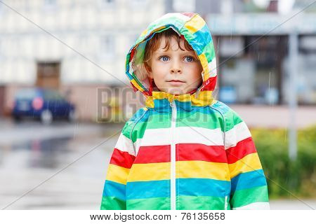 Happy Smiling Little Boy Walking In City Through Rain