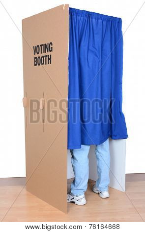 A man standing behind the curtain of a voting booth, The cardboard booth has a blue curtain to protect anonymity. Vertical format with a white background.