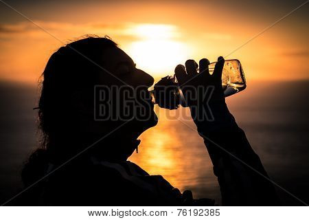 Silhouetted Woman Quenching Thirst With Water