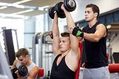 sport, fitness, lifestyle, powerlifting and people concept - group of men with dumbbells and personal trainer flexing muscles in gym poster