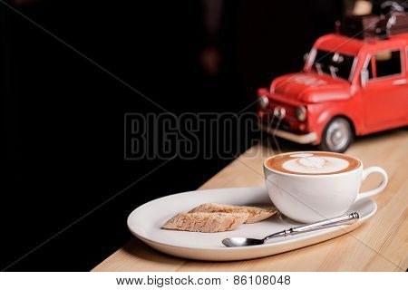 A nice view of capuccino and Italian pastries biscotti near red retro toy car on black background