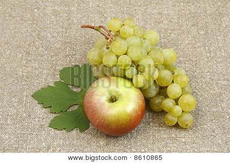 Bunch Of White Grapes And Apples On A Background Of The Matting