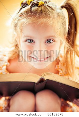 sweet happy little girl reading the book