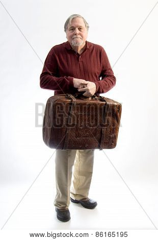 An Older Gentleman Wearing Khakis And A Sweater Holding An Antique Leather Suitcase