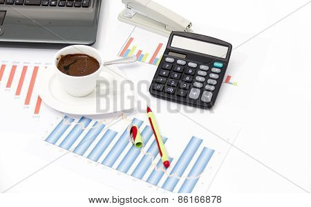 Analyzing Business Investment Charts With Calculator And Laptop