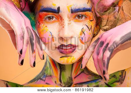 Beautiful fashion woman with bright color face art and body art.