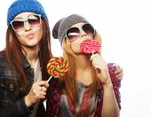 portrait of two young pretty hipster girls wearing  hats and sunglasses holding candys. Studio portrait of two cheerful best friends having fun and making funny faces. poster