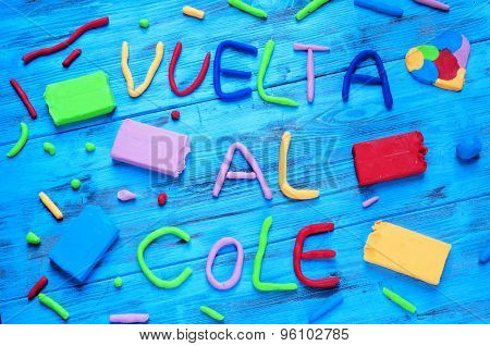 the sentence vuelta al cole, back to school in spanish, written with modelling clay of different colors, on a blue rustic wooden background