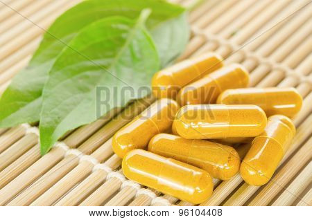 Yellow Herbal Medicine On Wooden Mat.