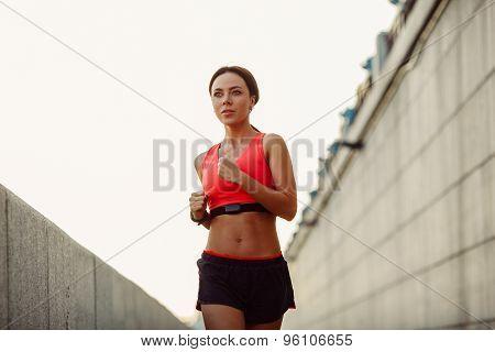 woman runnning along concrete wall