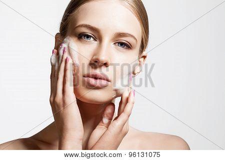 Young woman washing his face foam