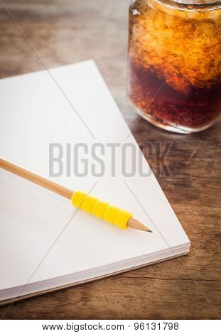 Pencil On Open Blank Notebook With Glass Of Iced Cola