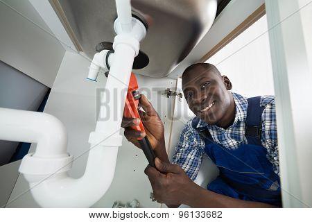 Handyman Repairing Sink Pipe