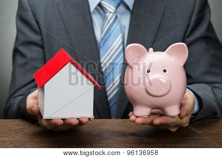 Businessperson With Piggy Bank And House Model