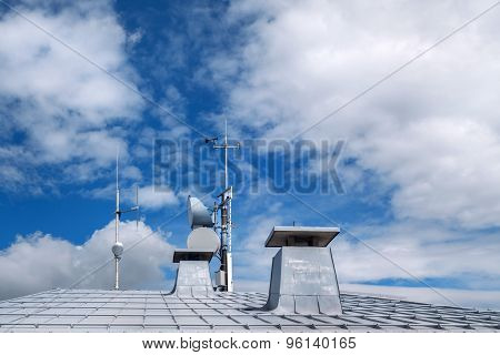 Metal roof with chimneys and antennas