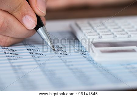 Person Hands With Pen And Calculator Over Report