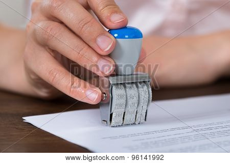 Person Hands Stamping Paper