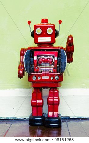 retro red robot toy on a wooden floor