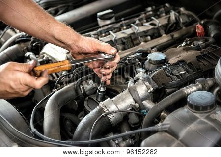 Mechanic Using A Wrench And Socket