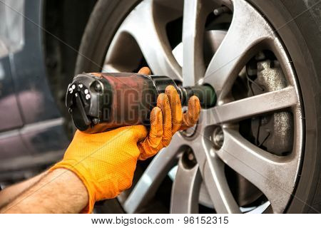 Mechanic Working On A Car Wheel