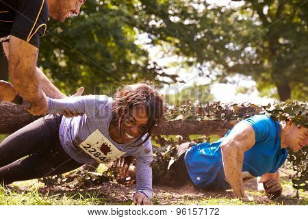 Assault course competitor helping others crawl under nets