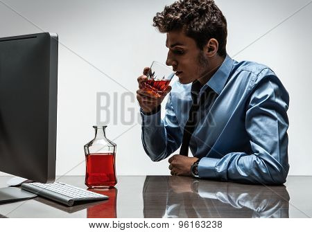 Young Alcoholic Man Drinking Whiskey Sitting Drunk At Office With Computer