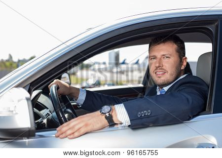 Attractive young man is driving to a business meeting