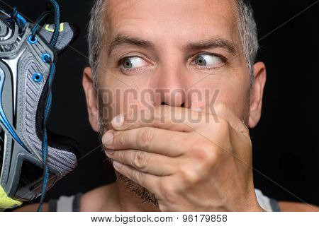 Man Covers Mouth After Smelling Shoe