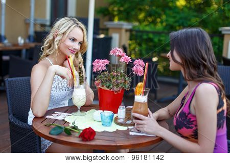 A Couple Of Women Drinking Cocktail In A Restaurant