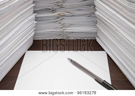 Pen And Blank Paper Besides Piles Of Documents