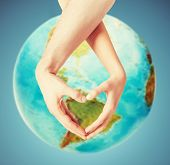 people, peace, love, life and environmental concept - close up of human hands showing heart shape gesture over earth globe and blue background poster