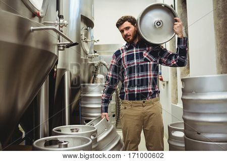 Portrait of young manufacturer carrying kegs in brewery