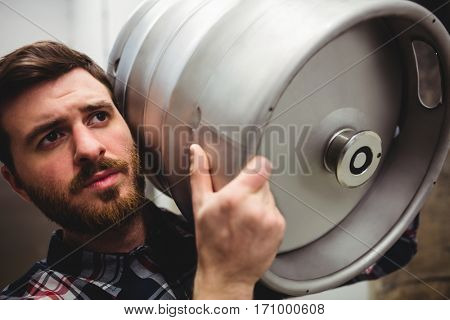 Close-up of manufacturer carrying keg in brewery