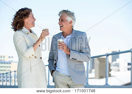 Happy mature couple enjoying coffee by railing in city