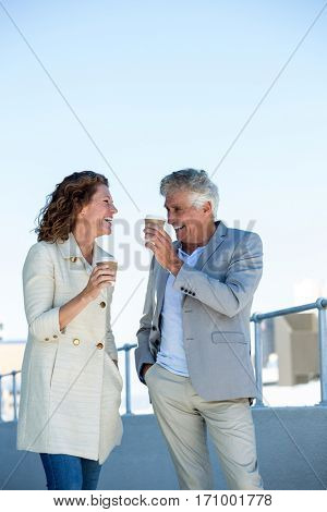 Happy mature couple enjoying coffee by railing against clear sky