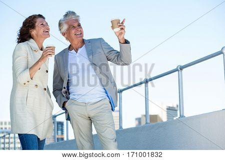 Joyful couple looking away by railing in city