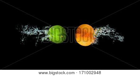 Fresh lime and orange in water with air bubbles water splash isolated on black