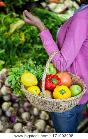 Mid section of woman holding fruits and vegetables in basket at organic section of supermarket