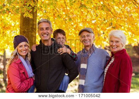 Portrait of happy multi-generation family standing at park during autumn