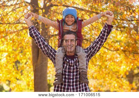Portrait of happy father carrying son on shoulder at park during autumn