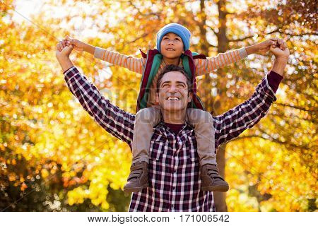 Cheerful father carrying son on shoulder against autumn trees