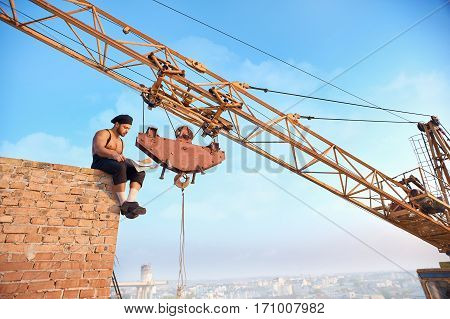 Handsome builder sitting on brick wall and reading news paper. Male with bare torso in work wear. Iron crane on background. Extreme building in hot weather.