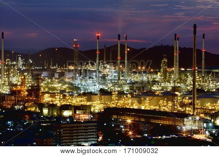Oil refinery with tube and oil tank at sunset