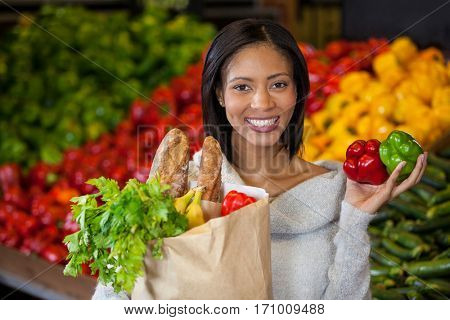 Portrait of woman holding vegetables in organic section of supermarket