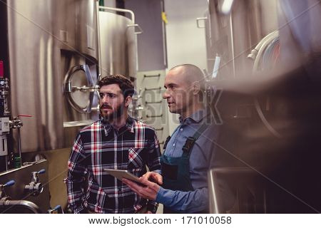 Owner and worker examining machinery at brewery
