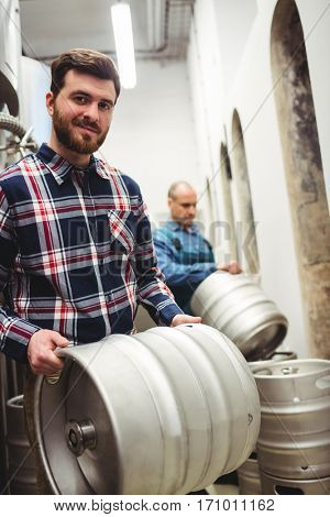 Portrait of confident owner carrying kegs at brewery